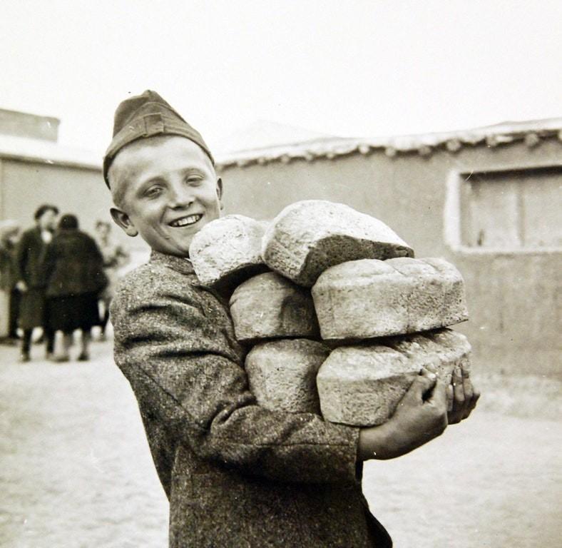 1943: bir tahliye kampında yapılan ekmek somunlarını taşıyan polonyalı genç ,tahran